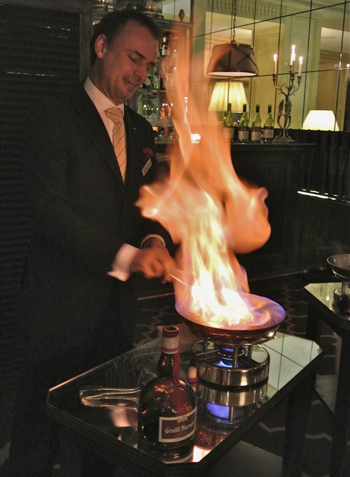 Le maitre d'hôtel en plein flambage de crête suzette flambée dans sa recette la plus traditionnelle: Remarque: Une crêpe Suzette est un dessert français créé par Auguste Escoffier composé d'une crêpe au beurre Suzette, une sauce à base de sucre caramélisé et de beurre, de jus de mandarine ou d'orange, de zeste et de liqueur Grand Marnier ou de Curaçao. Les crêpes Suzette sont généralement servies flambées, même si certains ouvrages de cuisine notent que dans la recette originale, elles sont servies non flambées.